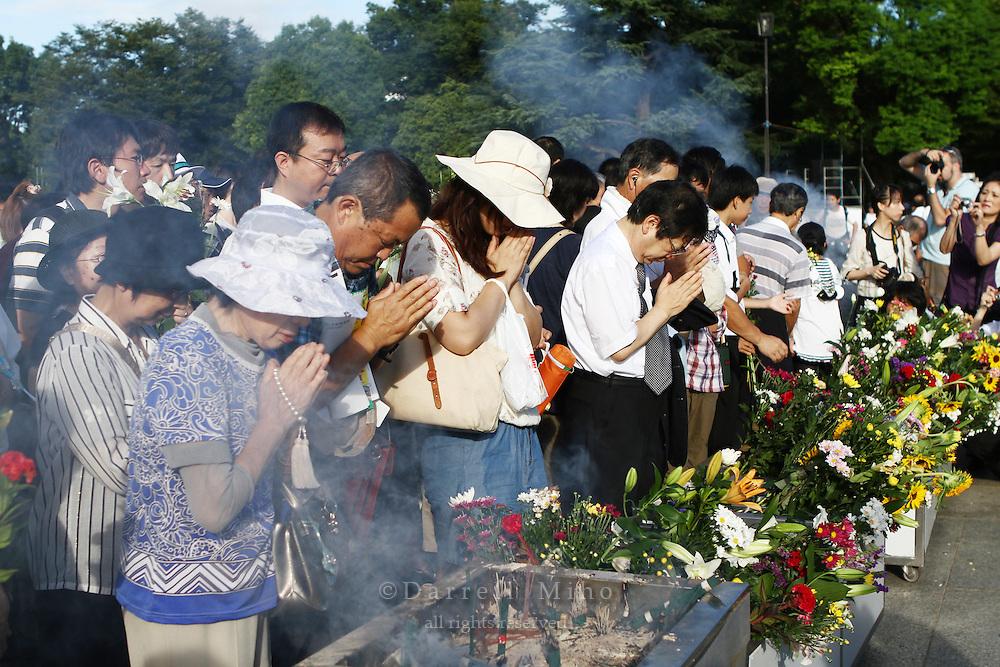 Aug. 06, 2010 ; Hiroshima, JPN - Visitors burn incense, offer flowers and pray at the 2010 Hiroshima Peace Memorial Ceremony in Peace Park.