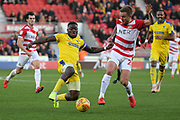 AFC Wimbledon defender Deji Oshilaja and Doncaster midfielder James Coppinger during the EFL Sky Bet League 1 match between Doncaster Rovers and AFC Wimbledon at the Keepmoat Stadium, Doncaster, England on 17 November 2018.