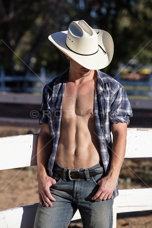 cowboy with an open shirt on a ranch