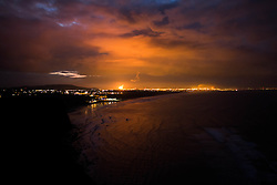 © Licensed to London News Pictures. <br /> 19/11/2014. <br /> <br /> Teesside, United Kingdom<br /> <br /> Viewed from Huntcliff near Saltburn the flames from an industrial chimney light up the night sky on Teesside. The region has a long history of heavy industry with towns and villages surrounding the area living in its shadow. <br /> <br /> Photo credit : Ian Forsyth/LNP