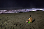 A man sits on the sand at Berawa beach, Canggu.