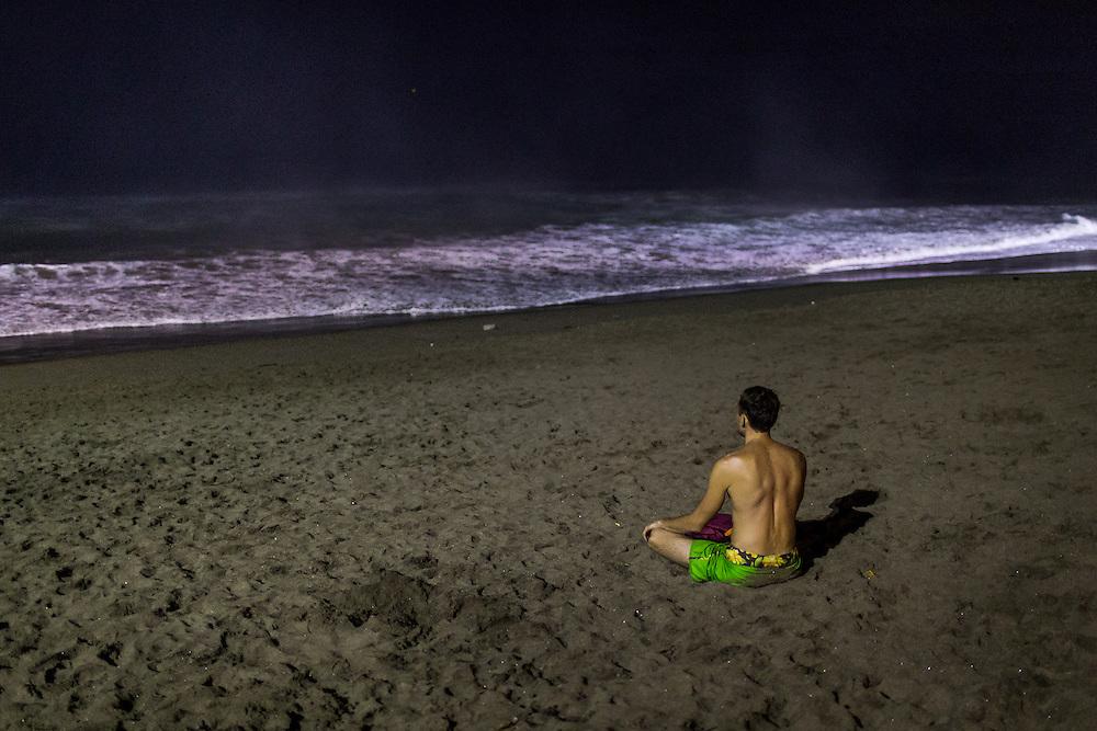 A man sits on the sand at Berawa beach, Canggu.