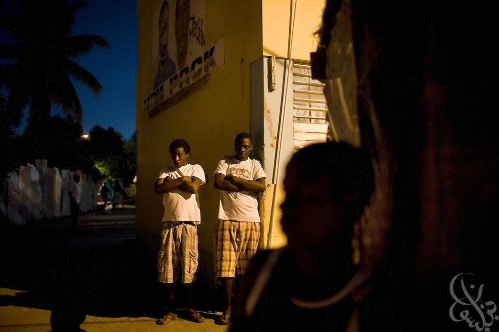 "Rema ""Action Pak"" garrison gang members stand watch as lookouts on a corner of their public housing scheme December 13, 2008 in the Trenchtown area of central Kingston. Because of the strength of ghetto gangs, often law enforcement is ill-equipped to enter or enforce rule of law in the garrisons of inner city Kingston. In the absence of legitimate law enforcement then, gangs fulfill a self-proclaimed community protector/enforcer role and function as defacto police, judge and juries on their turf."