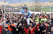 "Gold Cup winning jockey Jim Culloty riding race horse ""Best Mate"" makes his way triumphantly through the crowds at the Cheltenham National Hunt Festival."