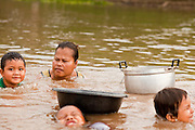 07 APRIL 2010 - NAKHON PHANOM, THAILAND:  Villagers collect shell fish in a channel in the Mekong River in Thailand. One of the women said the river is so low now that she can walk out into the channel and scrape the river bottom with her hands and feet for the mussels she uses in her soups. Normally the river flows completely through the river bed but it's currently running through a channel in the bottom of the river bed. According to people who live here, the river is at its lowest point in nearly 50 years. Many of the people who live along the river farm and fish. They claim their crops yields are greatly reduced and that many days they return from fishing with empty nets. The river is so shallow now that fisherman who used to go out in boats now work from the banks and sandbars on foot or wade into the river.     PHOTO BY JACK KURTZ