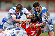 Workington Town interchange Joe Ryan (19) and Workington Town second row Kurt Maudling (12) tackle Keighley Cougars second row Josh Lynam (11)  during the Betfred League 1 match between Keighley Cougars and Workington Town at Cougar Park, Keighley, United Kingdom on 18 February 2018. Picture by Simon Davies.