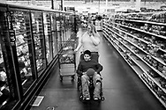 "Mary juggles Alex's wheelchair along with her cart while shopping at the Yuba City Walmart in March 2015. At 12 years-old Alex's 1q21.1 chromosome microduplication limits his mobility which make walking for long distances very hard on him. When Mary takes him out to he's wheelchair bound. Alex's extreme allergies also present issues for Mary since he's 100% allergic to dairy, wheat and nuts she must keep an eye on him constantly. If Alex touches any surface that may have even just the grease from a piece of cheese he will go into anaphylactic shock. To prevent this Mary will wipe down any parts of the shopping cart Alex could touch. "" It's not the routine that makes it hard,"" Mary said ""I am used to that. It's the all the stares and the folks who obviously block up the aisle and make it hard to get the a disabled child's wheelchair by that makes it hard""."