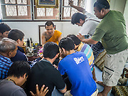 """22 MARCH 2013 - NAKHON CHAI SI, NAKHON PATHOM, THAILAND: Men pray and make offerings to a make after receiving sacred Sak Yant tattoos at Wat Bang Phra during the annual tattoo festival. Wat Bang Phra is the best known """"Sak Yant"""" tattoo temple in Thailand. It's located in Nakhon Pathom province, about 40 miles from Bangkok. The tattoos are given with hollow stainless steel needles and are thought to possess magical powers of protection. The tattoos, which are given by Buddhist monks, are popular with soldiers, policeman and gangsters, people who generally live in harm's way. The tattoo must be activated to remain powerful and the annual Wai Khru Ceremony (tattoo festival) at the temple draws thousands of devotees who come to the temple to activate or renew the tattoos. People go into trance like states and then assume the personality of their tattoo, so people with tiger tattoos assume the personality of a tiger, people with monkey tattoos take on the personality of a monkey and so on. In recent years the tattoo festival has become popular with tourists who make the trip to Nakorn Pathom province to see a side of """"exotic"""" Thailand. The 2013 tattoo festival was on March 23.   PHOTO BY JACK KURTZ"""
