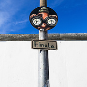 A sign in front of the Berlin wall indicating that you are at the end of the wall.