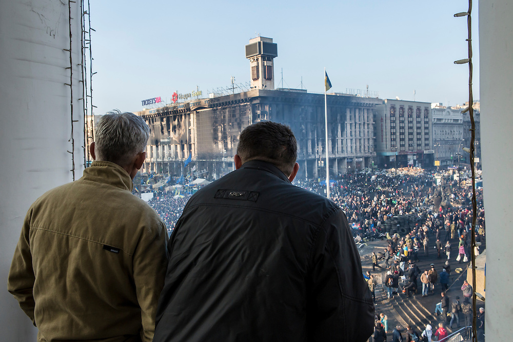 KIEV, UKRAINE - FEBRUARY 21: Men look out at a large crowd gathered on Independence Square on February 21, 2014 in Kiev, Ukraine. After a week that saw new levels of violence, with dozens killed, opposition and government representatives reached an agreement intended to resolve the crisis. (Photo by Brendan Hoffman/Getty Images) *** Local Caption ***