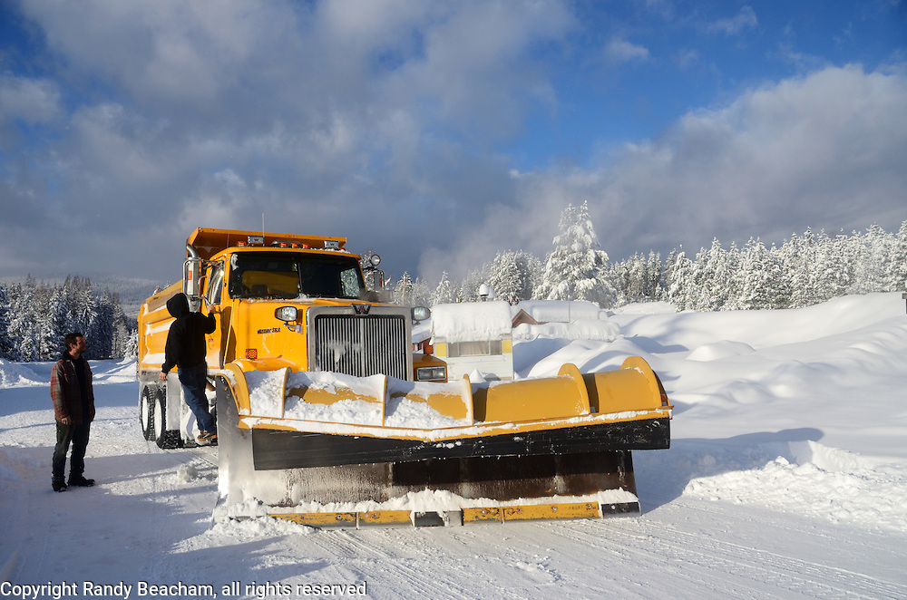 Lincoln County plow truck and driver talking to Yaak resident Duane Allan during historic February 2017 snowstorm that dumped as much as three feet of snow over a three day period. Yaak, northwest Montana.