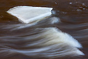The Tahquamenon River flows around ice in the river upstream from Upper Tahquamenon Falls in Tahquamenon Falls State Park, Michigan. The Tahquamenon River's brown color comes from tannic acid generated by organic material from cedar, hemlock and spruce trees along its banks. The golden light of sunrise reflecting on the river intensifies that color in this image.