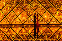 Lovers embrace in front of The Louvre Pyramid (Pyramide du Louvre). It is a large glass and metal pyramid designed by Chinese-American architect I. M. Pei, surrounded by three smaller pyramids, in the main courtyard (Cour Napoléon) of the Louvre Palace (Palais du Louvre) in Paris. The large pyramid serves as the main entrance to the Louvre Museum. Paris, France.