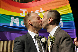 © Licensed to London News Pictures. 29/03/2014; Bristol, UK.  The first gay marriage in Bristol takes place following a change in the law to allow same sex marriage.  Mike McBeth (left) and Matthew Symonds (right) got married at Bristol Register Office, accompanied by their dog Zoly (a Hungarian vizsla) and family and friends.  The couple left on a chartered London Bus.<br /> Photo credit: Simon Chapman/LNP