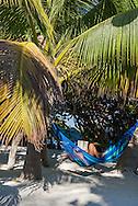 A woman reads in a hammock at a beachfront boutique hotel, Villa Pescadores, in Tulum, Mexico.