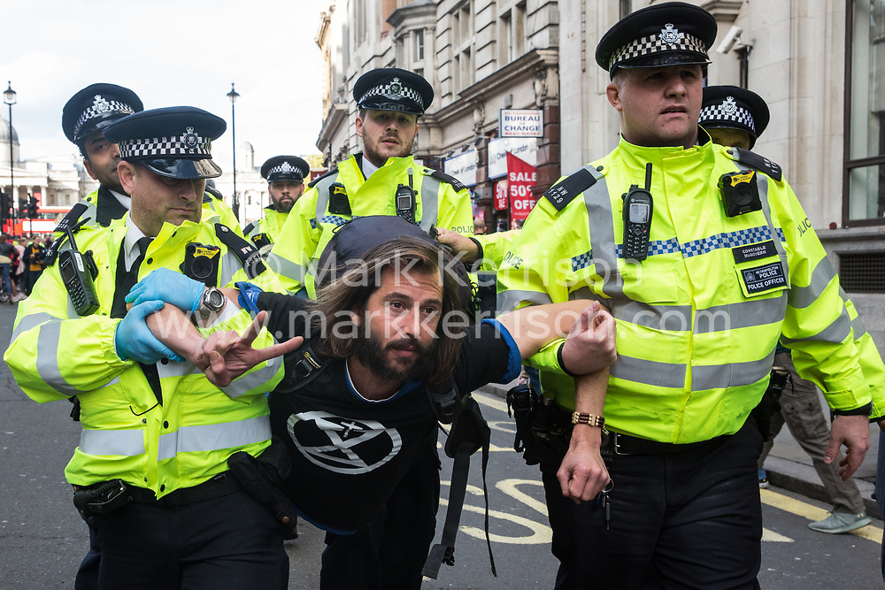 London, UK. 16 October, 2019. Police officers arrest George Barda from Extinction Rebellion who had defied the Metropolitan Police prohibition on Extinction Rebellion Autumn Uprising protests throughout London under Section 14 of the Public Order Act 1986 by sitting in the road in Whitehall.