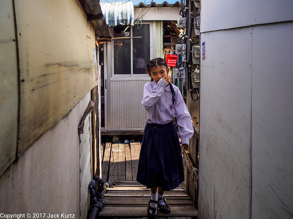 "20 JUNE 2017 - BANGKOK, THAILAND: A schoolgirl walks home in a community along the Chao Phraya River south of Krung Thon Bridge. This is one of the first parts of the riverbank that is scheduled to be redeveloped. The communities along the river don't know what's going to happen when the redevelopment starts. The Chao Phraya promenade is development project of parks, walkways and recreational areas on the Chao Phraya River between Pin Klao and Phra Nang Klao Bridges. The 14 kilometer long promenade will cost approximately 14 billion Baht (407 million US Dollars). The project involves the forced eviction of more than 200 communities of people who live along the river, a dozen riverfront  temples, several schools, and privately-owned piers on both sides of the Chao Phraya River. Construction is scheduled on the project is scheduled to start in early 2016. There has been very little public input on the planned redevelopment. The Thai government is also cracking down on homes built over the river, such homes are said to be in violation of the ""Navigation in Thai Waters Act."" Owners face fines and the possibility that their homes will be torn down.              PHOTO BY JACK KURTZ"