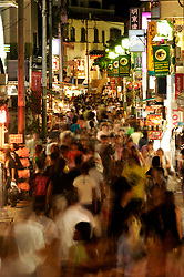 Motion blur image of crowds of people in Takeshita Street at night in trendy Harajuku District of Tokyo Japan