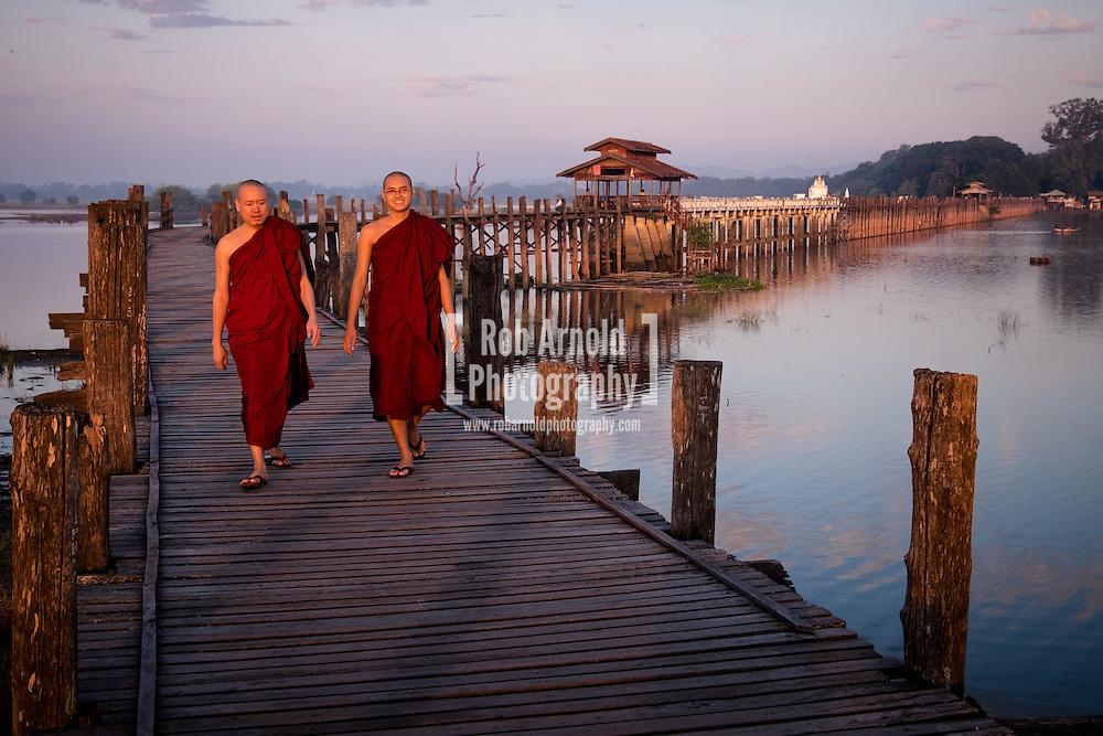 Two monks walk at sunrise across the wooden U Bein's Bridge near Amapura in Mandalay.