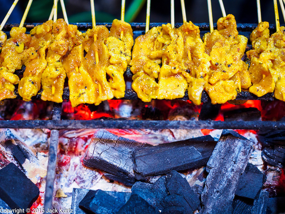 26 MAY 2015 - BANGKOK, THAILAND: Chicken satay grills at small restaurant on Sukhumvit Soi 38 in Bangkok. The food carts and small restaurants along Soi 38 have been popular with tourists and Thais alike for more than 40 years. The family that owns the land along the soi recently decided to sell to a condominium developer and not renew the restaurant owners' leases. More than 40 restaurants and food carts will have to close. The first wave of closings could start as soon June 21 and all of the restaurants are supposed to close over the next several months.     PHOTO BY JACK KURTZ