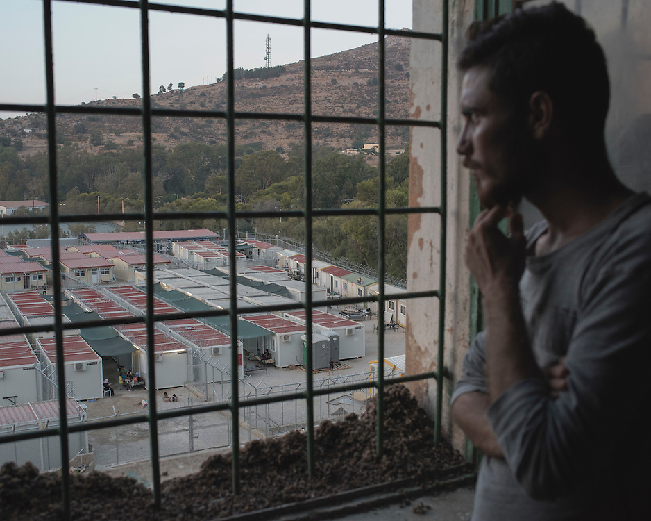 Yazidi Hazim Elias Khadeda, 22, looking at the Leros 'Hotspot', an EU-run migrant's reception centre opened in the grounds of the former Lepida psychiatric hospital (from which the view is taken).<br />