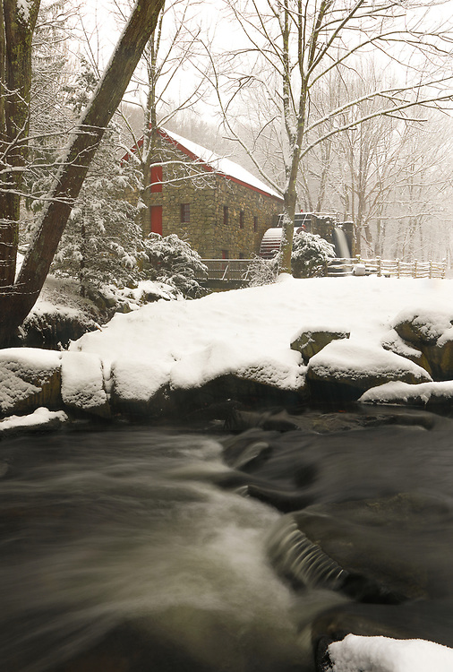 The Wayside Inn Grist Mill in Sudbury Massachusetts during a New England snowstorm in winter. A long exposure photography setting conveys the flowing water of the brook in the front and the falling waters across the Grist Mill.<br />