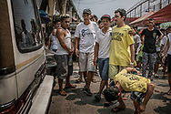 "Incarcerated brothers of Junmar Abletes, killed in an extrajudicial killing as part of Duterte's ""War on Drugs"", are led handcuffed by their father Pedro out of the Navotas City Jail to a hearse for a final farewell to their brother.  Mario, 21, jailed for theft doubles over in emotional pain while Roland, 30, incarcerated for a drug offense, react differently to brother""s death.  Navotas, Meto Manila, Philippines."