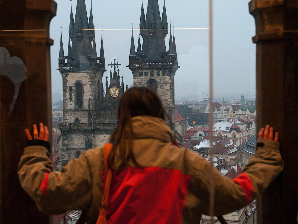 Eine junge Frau betrachtet das Prager Stadtpanorama und die Teynkirche vom Turm des Altst&auml;dter Rathaus an einem verschneiten Tag in Prag.<br /> <br /> A young woman is looking from the tower at the Old Town City Hall to the Teyn church at Old Town Square covered with snow in the city center of Prague.
