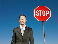 Businessman standing next to stop sign half length