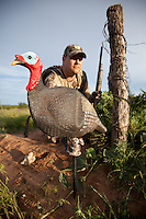 TURKEY HUNTER SETTING UP A JAKE DECOY NEAR A BARBED WIRE FENCE