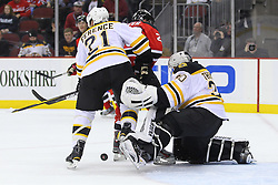 Jan 4, 2012; Newark, NJ, USA; Boston Bruins goalie Tim Thomas (30) makes a save through a screen by New Jersey Devils center Ryan Carter (20) during the second period at the Prudential Center.