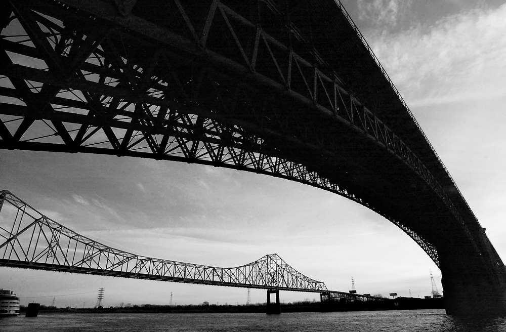"""The Martin Luther King Bridge (formerly known as the Veterans Bridge) is seen below the arch of the Eads Bridge in St. Louis. The MLK Bridge is a cantilever truss bridge of about 4000 feet in total length across the Mississippi River, connecting St. Louis with East St. Louis, Illinois. The bridge serves as traffic relief connecting the multiplexed freeways of Interstate 55, Interstate 70, Interstate 64, and U.S. Highway 40 with the downtown streets of St. Louis..The Eads Bridge is a combined road and railway bridge over the Mississippi River at St. Louis, connecting St. Louis and East St. Louis, Illinois..The bridge is named for its designer and builder, Captain James B. Eads. When completed in 1874, the Eads Bridge was the longest arch bridge in the world, with an overall length of 6,442 feet (1,964 m). The ribbed steel arch spans were considered daring, as was the use of steel as a primary structural material: it was the first such use of true steel in a major bridge project.[1].The Eads Bridge was also the first bridge to be built using cantilever support methods exclusively, and one of the first to make use of pneumatic caissons. The Eads Bridge caissons, still among the deepest ever sunk, were responsible for one of the first major outbreaks of """"caisson disease"""" (also known as """"the bends""""). Fifteen workers died, two other workers were permanently disabled, and 77 were severely afflicted.[2].The bridge was owned and operated by the Terminal Railroad Association of St. Louis from the 1890s until 1989 when it was swapped for the MacArthur Bridge (St. Louis).[3].The Eads Bridge is still in use, and stands on the St. Louis riverfront between Laclede's Landing on the north and the grounds of the Gateway Arch to the south. Today the road deck has been restored, allowing vehicle and pedestrian traffic to cross the river. The rail deck has been in use for the St. Louis Metrolink light rail line since 1993.  Photo by Lance Cheung"""