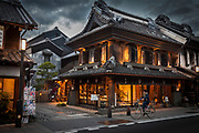 Cyclist rides past craft shop at dusk, rain storm approaches, Magome, near Tokyo, Japan.