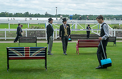 © Licensed to London News Pictures. 18/06/2014. Ascot, UK. Two men dressed in morning suits sit on a bench featuring the Union Flag whilst members of the Ascot House Keeping staff look on.  Day two at Royal Ascot 18th June 2014. Royal Ascot has established itself as a national institution and the centrepiece of the British social calendar as well as being a stage for the best racehorses in the world. Photo credit : Stephen Simpson/LNP