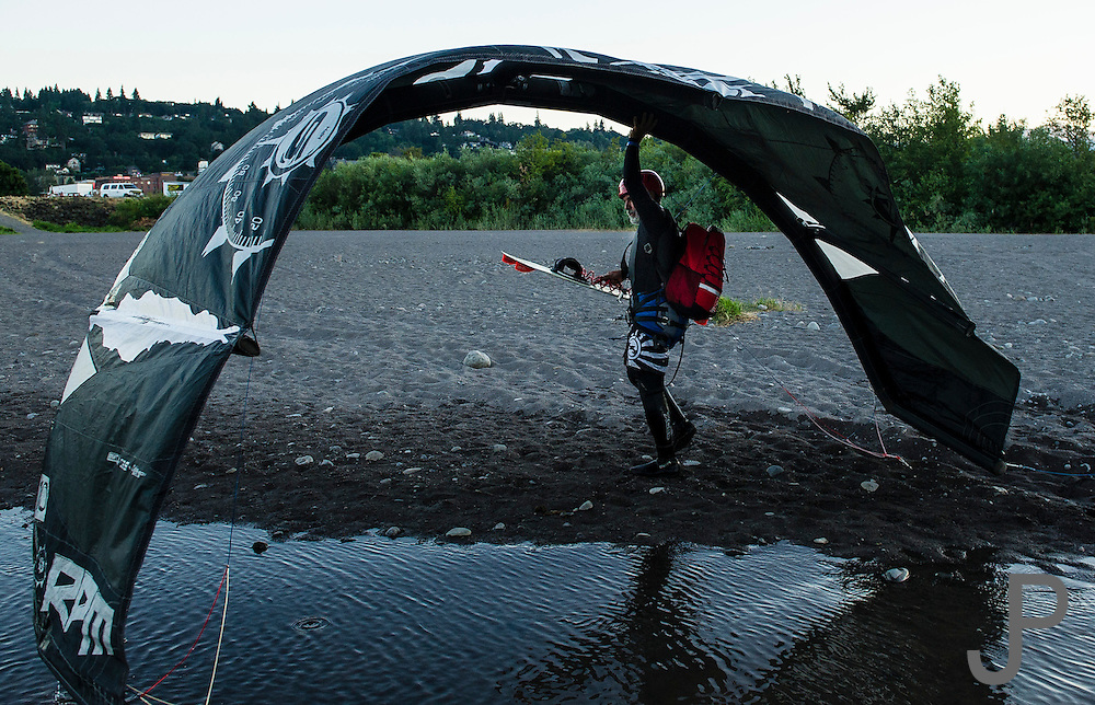 Alfonso Jimenez carrying his kite and board from the water at Hood River, Oregon.