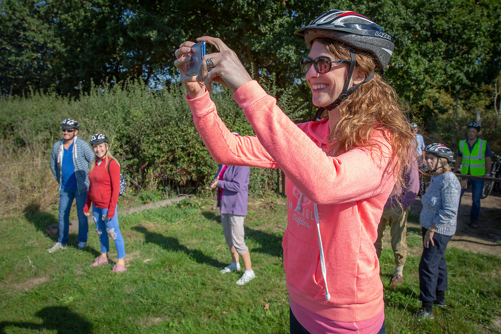 A happy woman takes a photo on her phone in a field while taking a break on a cycling tour around Staplehurst, Kent, England, UK.  (photo by Andrew Aitchison / In pictures via Getty Images)