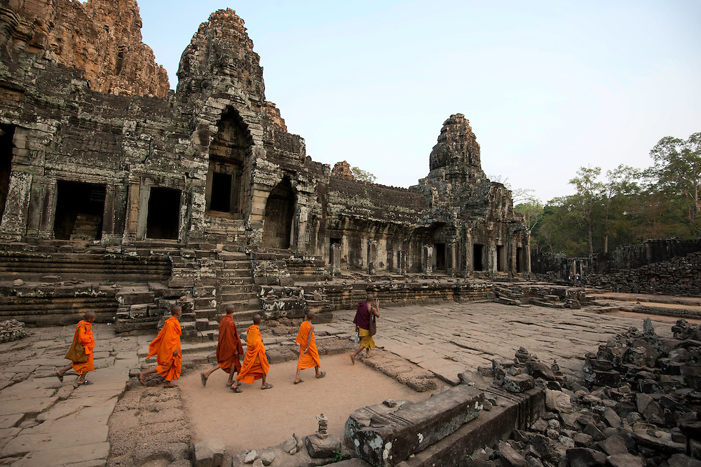 Novice buddhist monks make pilgrimage to the Bayon at the centre of Angkor Thom.