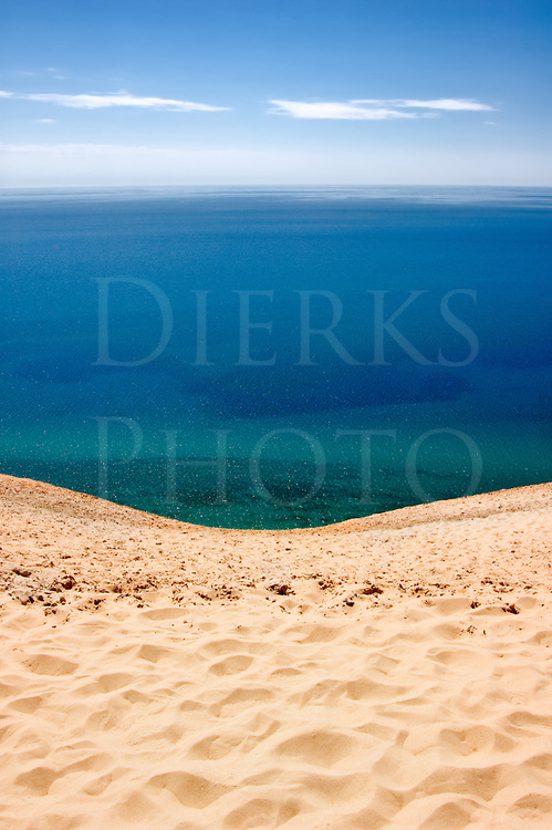 This is the view of Lake Michigan from 450 feet high at Sleeping Bear Dunes National Lakeshore. It is simply stunning how much sand there is in Michigan. Standing here looking left and right, you see nothing but these gigantic sand dunes into the horizon both ways on the coast, and it is remarkable.<br /> <br /> At this height, you can see the slight curvature of the earth in the horizon about 25 miles out. You can also see the depth of the water change from green at the shallow shore change into deeper blue going out into the lake.