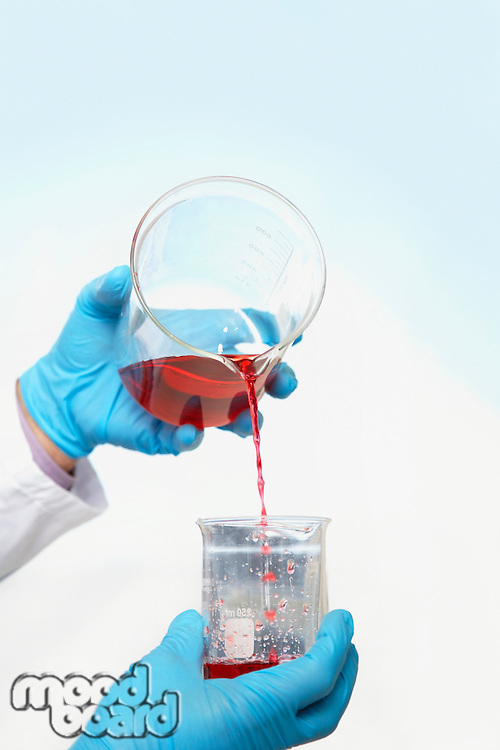 Scientist pouring red liquid into beaker close-up of hands