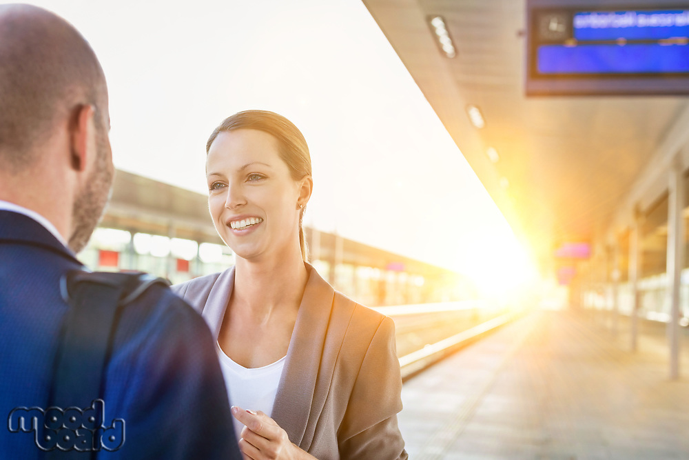 Portrait of businessman and businesswoman holding cup of coffee while talking and waiting for the train