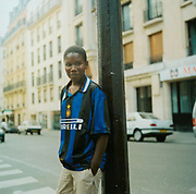 Young teenager standing by a lamp post in Paris wearing a football strip