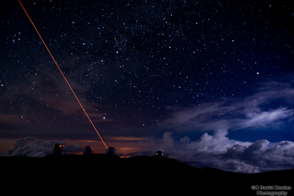 The Keck Laser Guide Star and a valley thunder storm add to the night sky on the summit of Mauna Kea