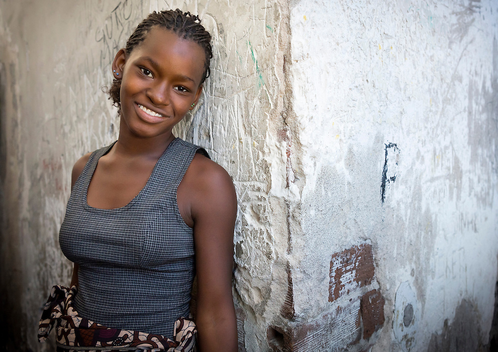 Grande Hotel slum, Beira, Mozambique. Rosanna wears a huge smile on her face. At 16 years old, she dreams to leave this place, become a teacher and get a real house. She is in a hurry to get to the beauty salon located at<br /> the ground floor of the hotel.<br /> <br /> Built in 1954, the Beira Grande Hotel in Mozambique was once the most luxurious hotel in Africa. Meant for wealthy businessmen and tourists, it was both the pinnacle of luxury and of colonial folly. The giant complex had around 120 suites, a cinema, an Olympic swimming pool, a helicopter pad, restaurants, a bank, a post office - it was a city in itself. For its massive size, 120 rooms is really not much. Turns out there was no demand so they shut it down in 1963. It never made a profit. Since shutting down, this colonial dream has become a nightmare. &Alpha;fter being used initially as military base during Mozambique&rsquo;s civil war (1977 &ndash; 1992), the squatters moved in. The people who live there have mostly emigrated from the mine-filled countryside. The living conditions are atrocious. Drugs, disease, and trash are ubiquitous. People have removed much of the plumbing, electrical, windows and even concrete to sell on the black market. This weakens the building but provides them with another meal. Walking through the Grande Hotel, you come face to face with the folly of colonialism and the tragic legacy it left behind. The grandeur and luxury has been left to rot into a nightmare. The hope of the independence era in Africa has long left this place. The one thing every resident shares is the desire to leave.