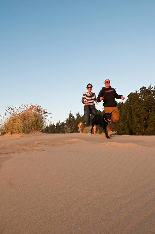 Oregon Dunes National Recreation Area: Couple running with dogs at dunes overlook day use area south of Florence.