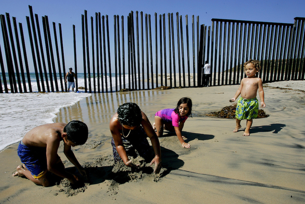 TIJUANA, MEXICO:  Kids play on the beach with the border wall in back in the Las Playas area of Tijuana