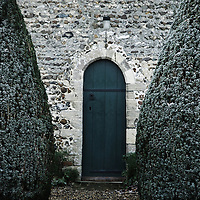 A gravel path between two yew trees to a church door