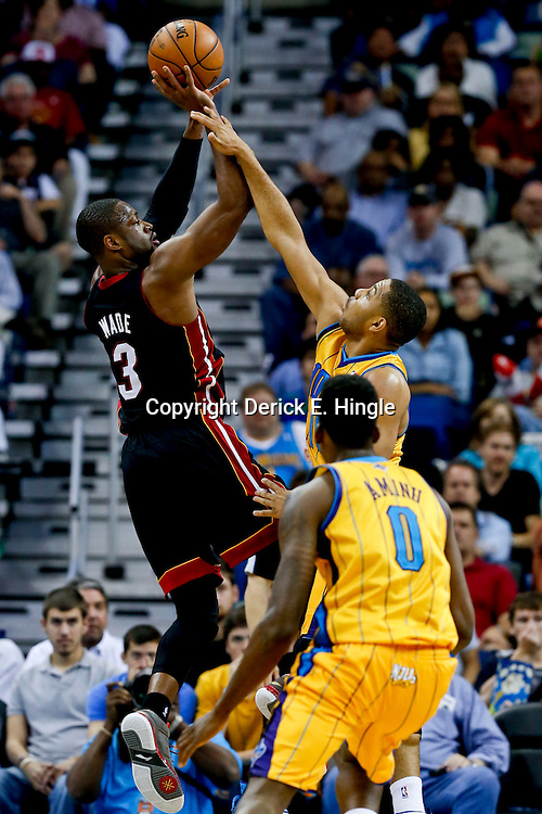 Mar 29, 2013; New Orleans, LA, USA; Miami Heat shooting guard Dwyane Wade (3) shoots over New Orleans Hornets shooting guard Eric Gordon (10) and small forward Al-Farouq Aminu (0) during the first quarter of a game at the New Orleans Arena. Mandatory Credit: Derick E. Hingle-USA TODAY Sports
