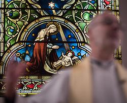 24 November 2019, Geneva, Switzerland: Stained glass scene, behind Rev. Michael Rusk, who presides over Sunday service at the Emmanuel Episcopal Church, Geneva.