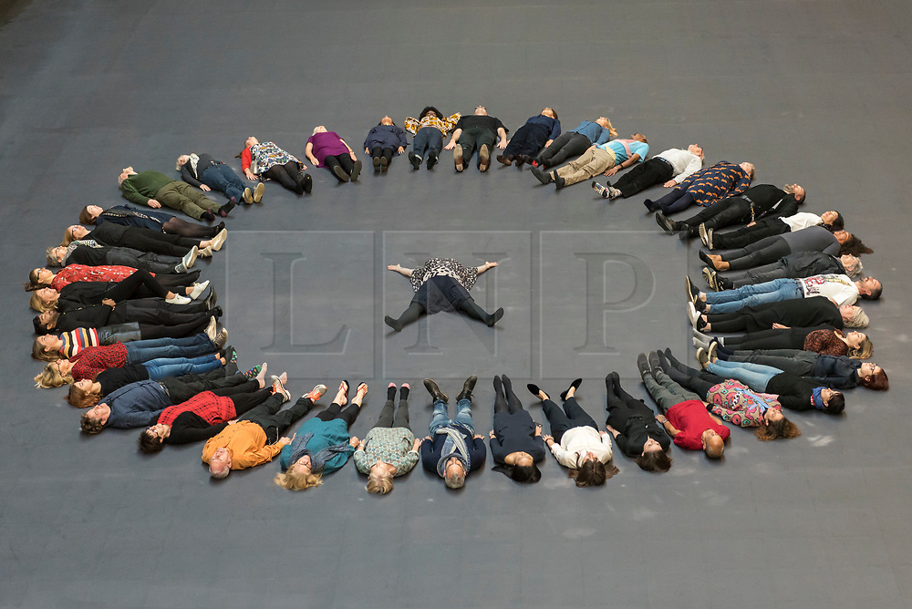 "© Licensed to London News Pictures. 01/10/2018. LONDON, UK. Tania Bruguera (centre) and volunteers prepare to create body impressions on the heat-sensitive floor. Unveiling of the this year's Hyundai Commission by Cuban artist and activist Tania Bruguera at Tate Modern.  The work is called ""an ever-increasing figure"", which represents the scale of mass migration and the risks involved.  Visitors are invited to interact with the work which comprises a heat-sensitive floor, which includes a portrait of a person's face beneath, combined with low frequency sounds.  The work is on display 2 October to 24 February 2019..  Photo credit: Stephen Chung/LNP"