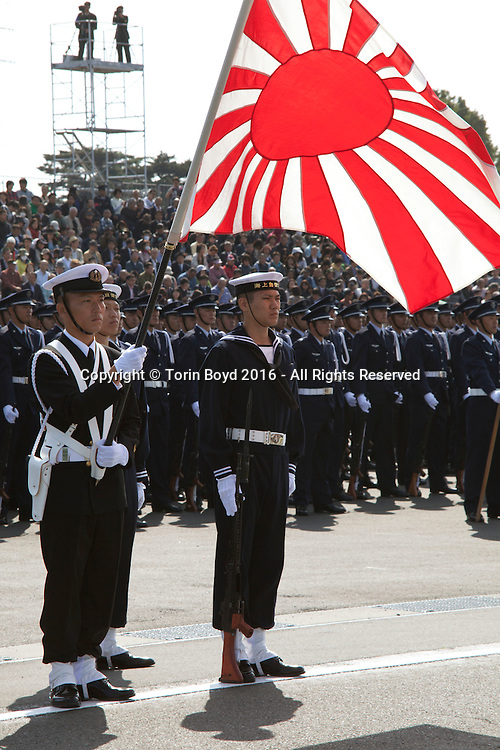 October, 23, 2016, Asaka, Saitama Prefecture: Flying the old and traditional rising sun flag, members of the Japan Maritime Self Defense Force flaunt their colors during an annual military review held at the Asaka Training Area, a Japan Ground Self Defense Force (JSDF) base on the outskirts of Tokyo. For this event, Prime Minister Shinzo Abe, top ranking Japanese brass and international dignitaries were in attendance to view Japan's military might. This included 4000 troops, 27 divisions, 280 vehicles and artillery, plus 50 aircraft of the Ground, Air, and Maritime branches of the JSDF. (Torin Boyd/Polaris).